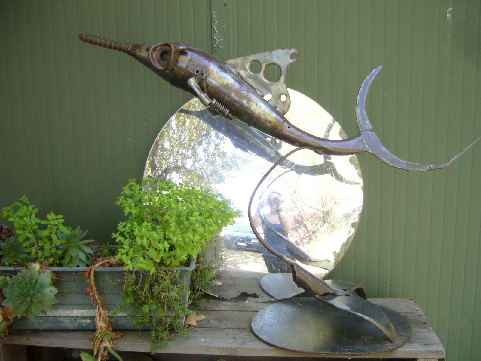 Magnifica scultura rappresentante fauna ittica creata con materiale di recupero, tra cui una marmitta per scooter ed altri elementi metallici.