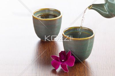 water being poured from kettle to cup - Tea kettle with cups and flower on wooden table