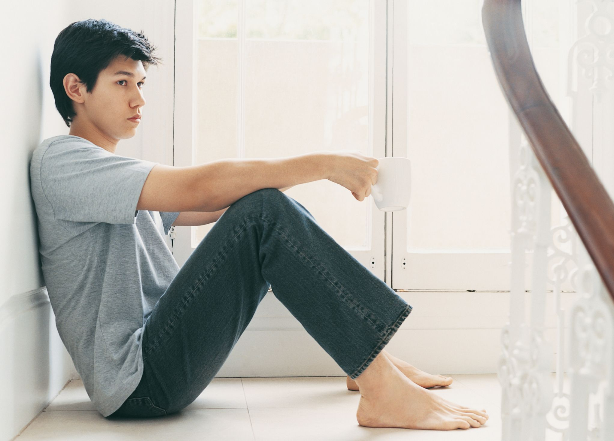 Man Sits On A Tiled Floor Leaning On A Wall Holding A Cup Sitting Poses Lean Men Bipolar Symptoms In Men