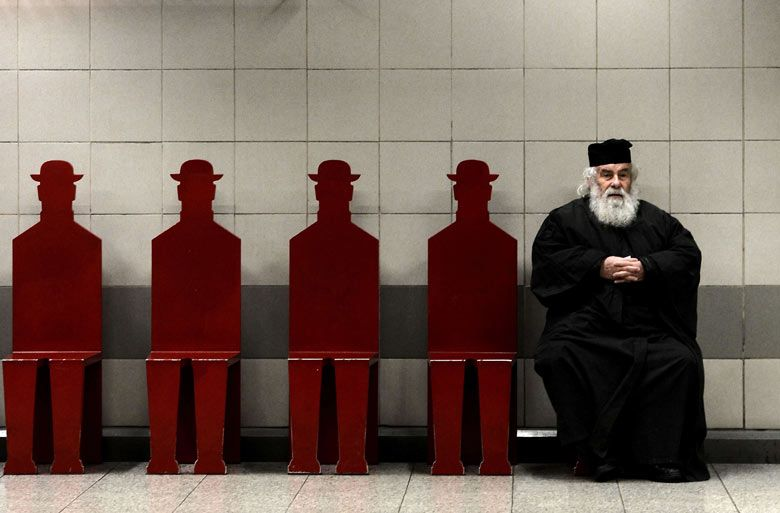 a greek orthodox priest sits on a bench in an athens metro station