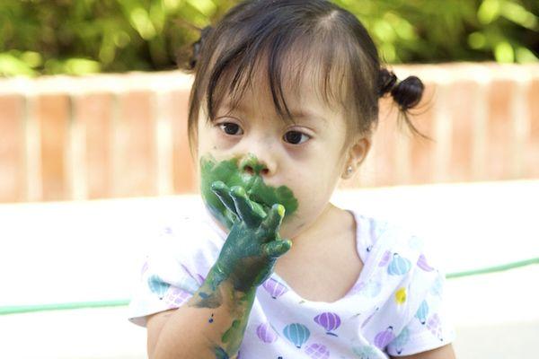 Niñita con síndrome de Down jugando con pintura
