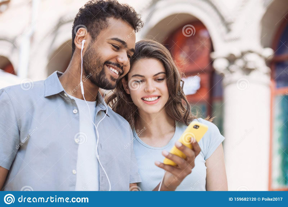 Beautiful Happy Couple Using Smartphone Young Joyful Smiling Woman And Man Looking At Mobile Phone In A City Technology Happy Couple Men Looks Mobile Phone
