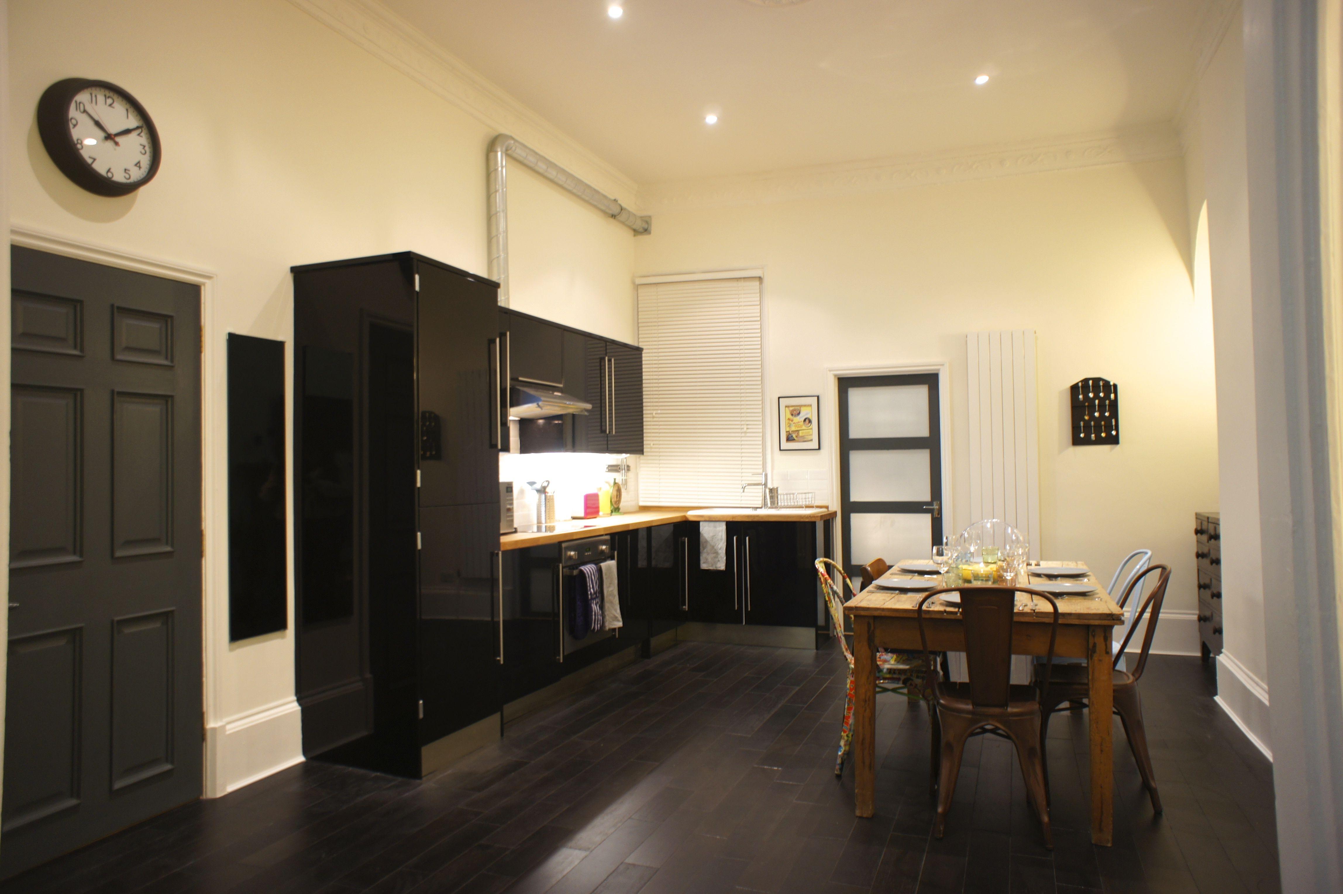 Black gloss kitchen, dark floors, farmer table, mismatched