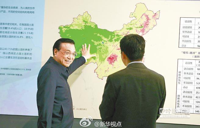 大陸國務院總理李克強(左)指著中國大陸地圖上的「胡煥庸線」,盼解決東西城鄉差距問題。(取自新浪微博@新華視點)