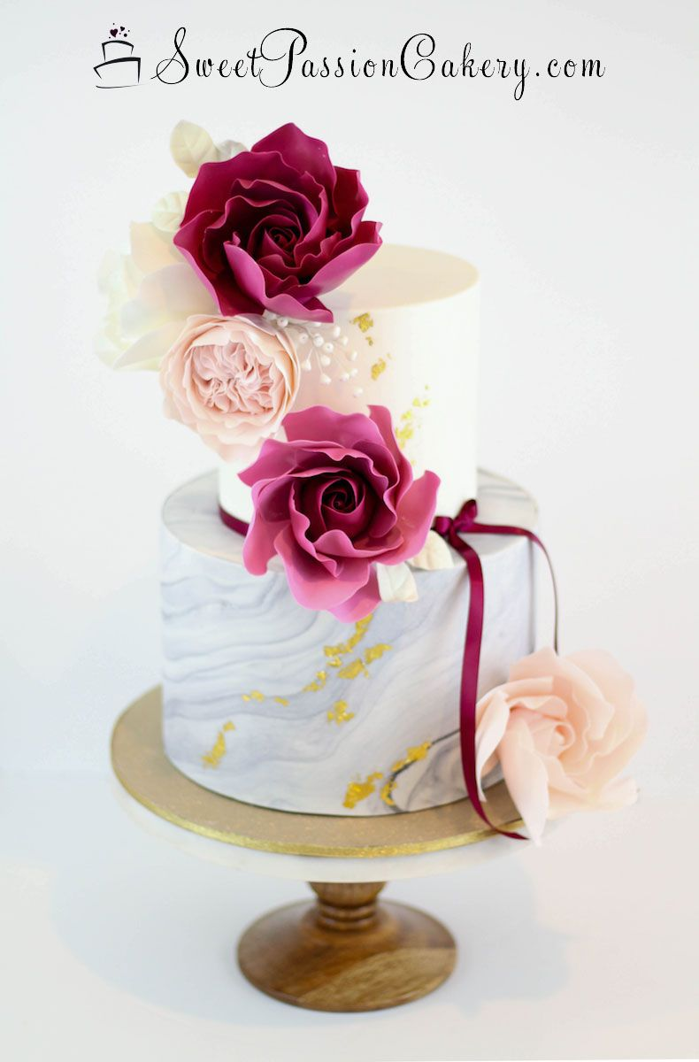 A beautiful white and gray marble cake with deep burgundy pink and