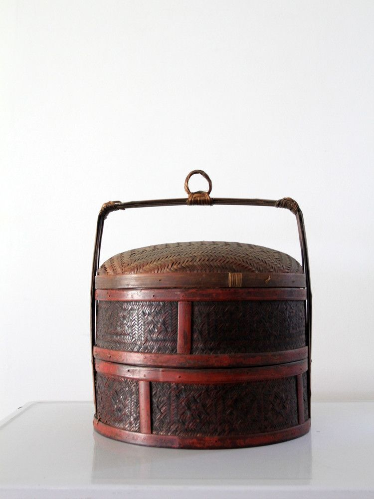 This is an antique Chinese wedding basket. Woven reeds shape the basket with black, red, and brown tones and are set in a bamboo frame. It is a two compartment tiered basket and features a woven ring