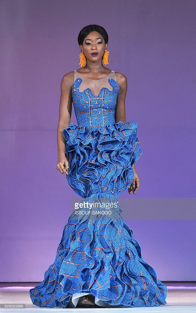 Models present a creation by label Celine Koby during a fashion show marking the 170th anniversary of Dutch manufacturer of African luxury VLISCO in Abidjan on November 26, 2016. / AFP / ISSOUF