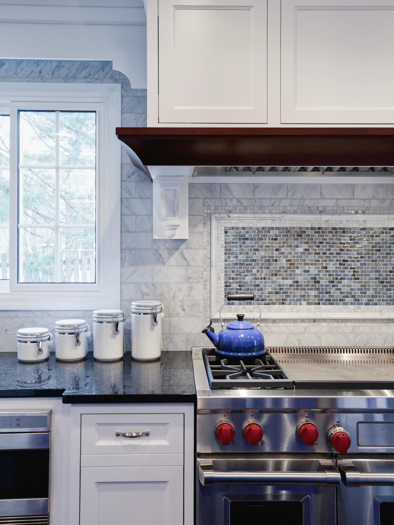 A wall of marble subway tile forms into a framed blue and brown a wall of marble subway tile forms into a framed blue and brown mosaic tile backsplash dailygadgetfo Choice Image