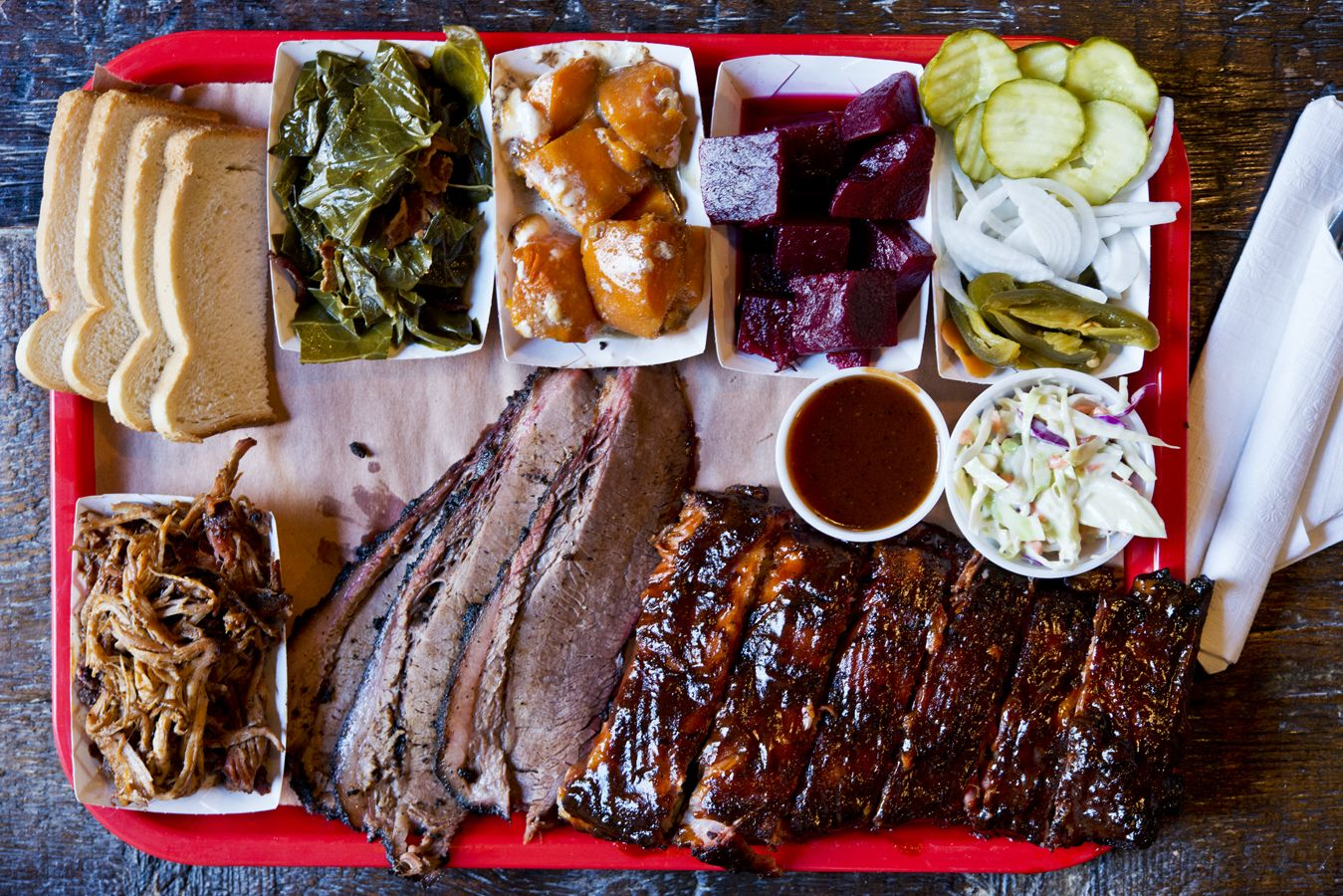 DELUXE PLATTER. Half slab St. Louis ribs, pulled pork, beef brisket. House pickled beets, collard greens, candied yams. Pickles, jalapenos, white bread, small cup of slaw.