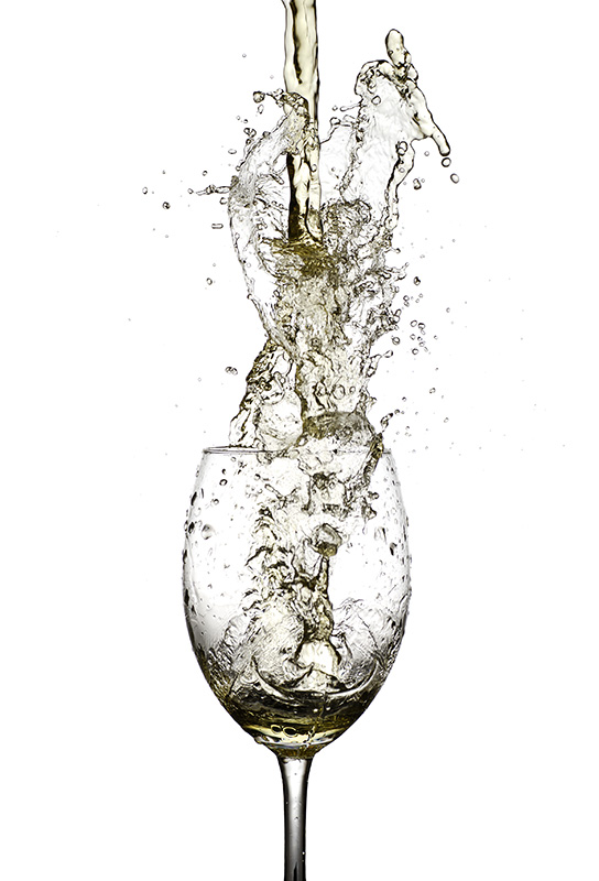 Wwhite Wine Being Poured In To A Wine Glass From A Height