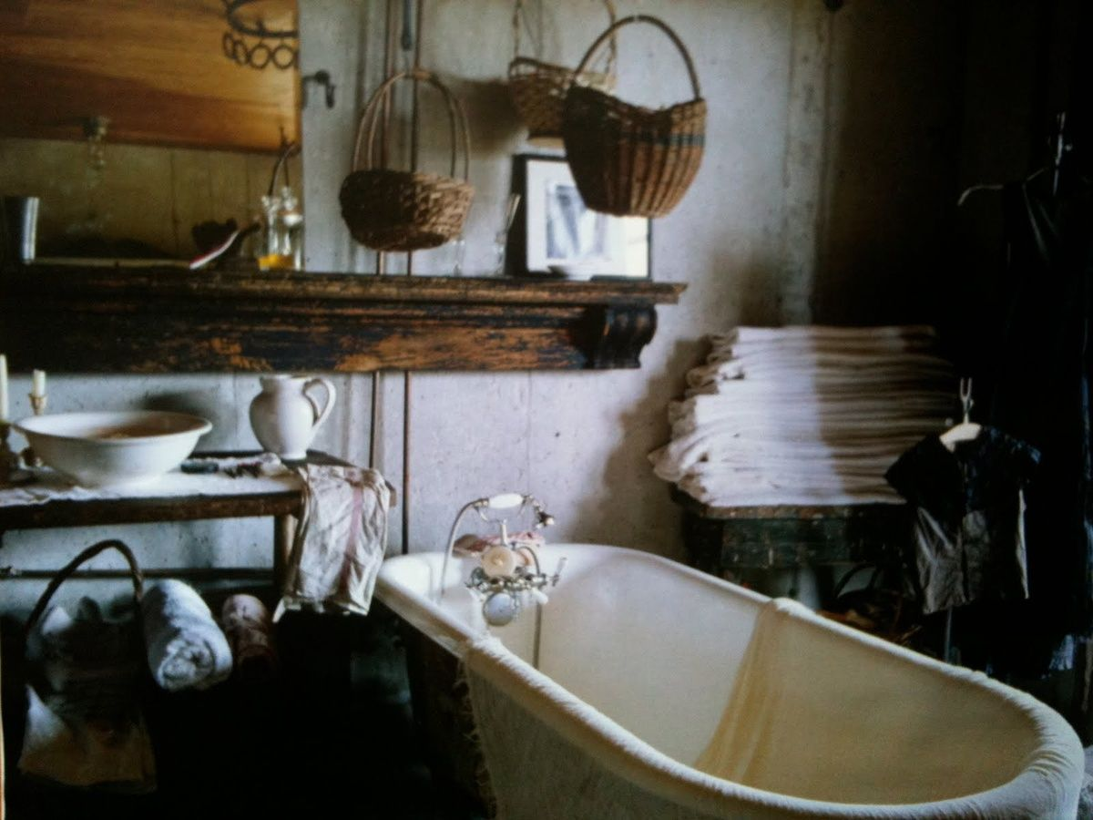 Rustic bathroom with Clawfoot tub, wood and baskets ...