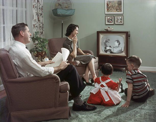 A happy family cheerfully sits in their living room and watches a televisied clown and puppet show 1957 The father holds an newspaper open to the...