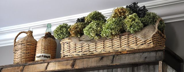 A Basket Full Of Dried Hydrangeas On Top Of A Cabinet Or Tall Piece Of Furnitur Decorating
