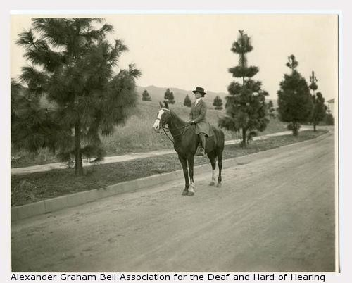 Helen Keller riding horseback on a pine tree-lined road.