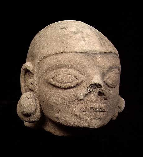 """TUMACO-LA TOLITA POTTERY DEATH HEAD, ca. 300 BC. The head with grinning teeth and large ear spools, remains of painted designs on the headdress. 2.5"""""""