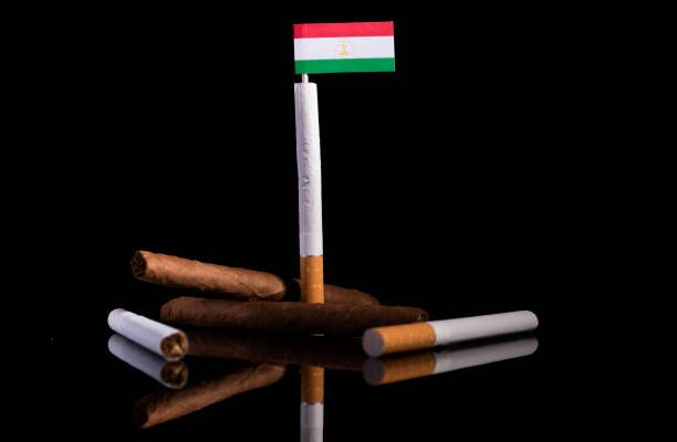 tajikistan flag with cigarettes and cigars tobacco industry concept