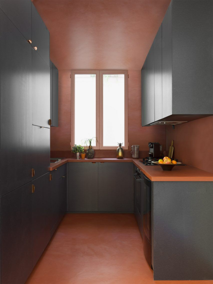 The Kitchen Features A Bold Use Of Colour Blocking Dark Grey Cabinets Stand Out Against A Soft Red Parisian Apartment Elegant Interior Design Kitchen Flooring