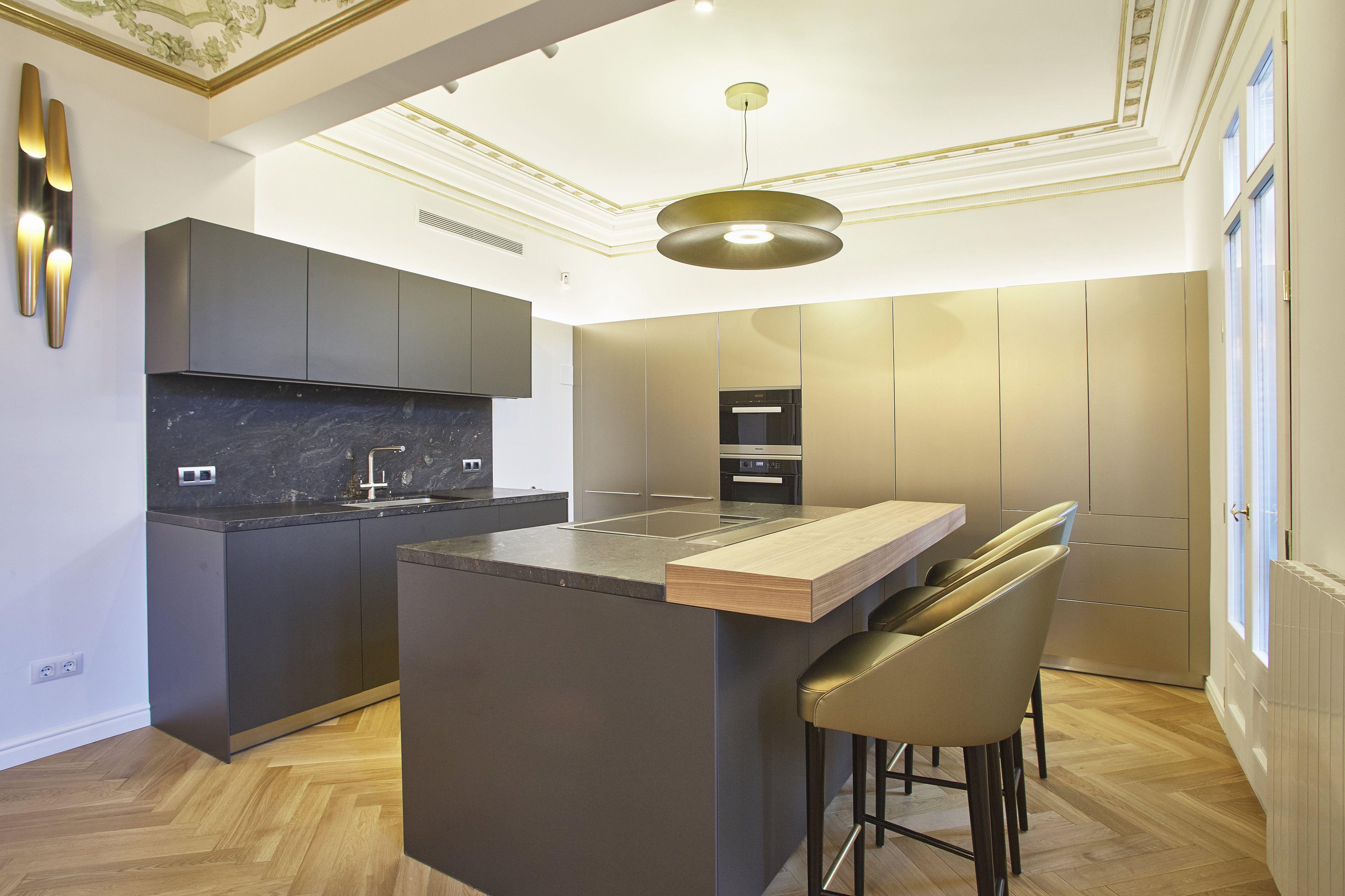 Cocina con isla color negro y barra comedor de madera y armarios con ...