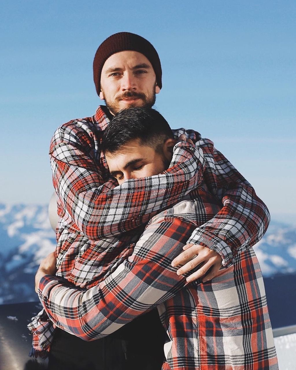 Loving male gay couple hugging outside in city street, stock photo