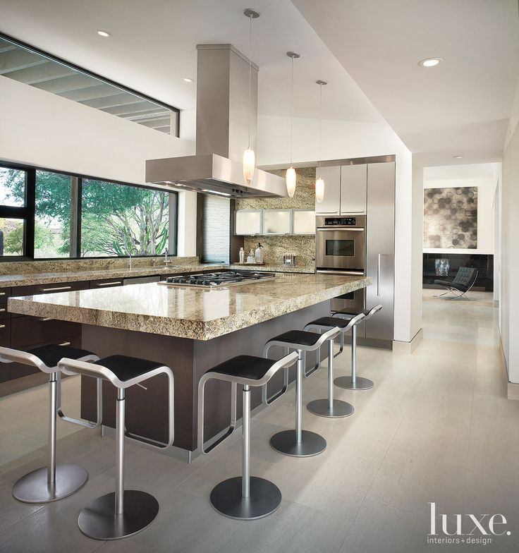 Equipped with an extra large island, this contemporary kitchen features  rich, granite countertops and dark-stained, rift-cut white oak cabinetry.