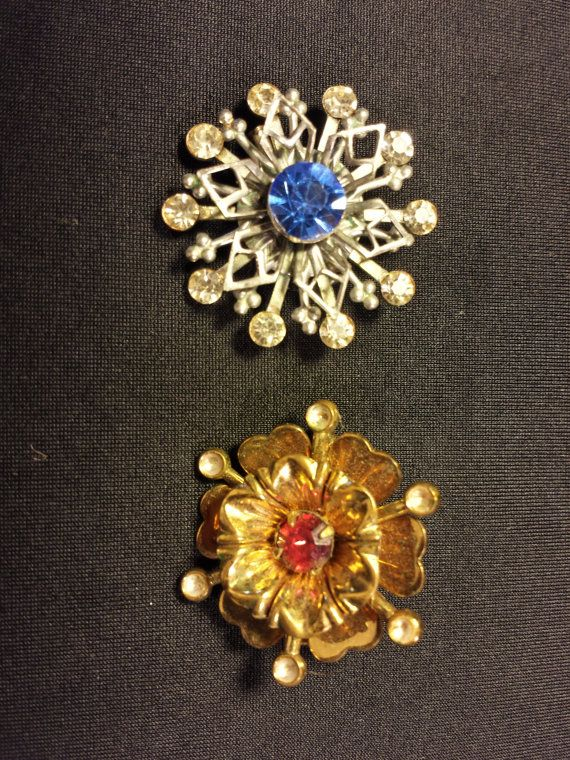 A blue gemstone snowflake brooch, excellent condition working clasp. It has a big blue stone in the center of a six pointed star, raised above a 10 prong rhinestone snow flake. I am guessing on the year, but Im pretty sure about it. Each brooch is approx. 1.5 inches around.  The gold toned brooch sort of looks like an open morning glory with a red gemstone in the center, sitting in a six petal dogwood bloom. This one is in good condition with a working clasp. It has six long stems that…