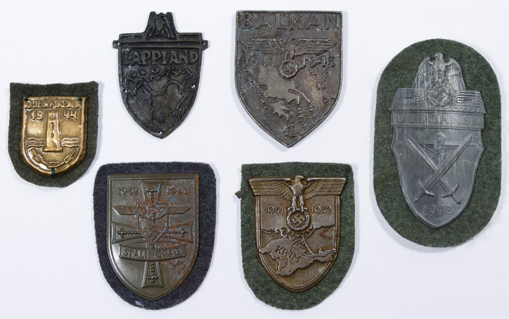 Lot 361: World War II German Sleeve Shield Assortment; Six Nazi items including Lappland, Balkan, Krim, Stalingrad, Demjansk and a small 1944 campaign shield