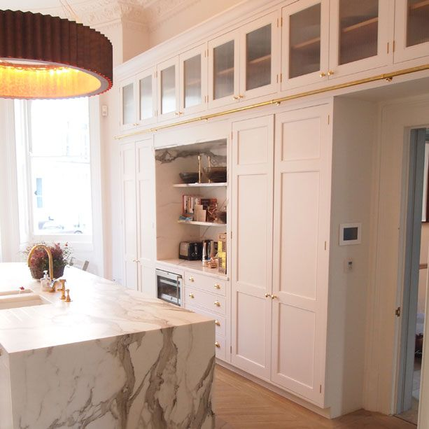 Townhouse Kitchen With A Large Marble Clad Island, This White And  Gold Themed