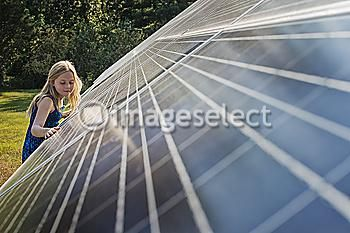 http://www.imageselect.eu/en/media/viewImage/70206073/A-young-girl-standing-beside-and-leaning-against-a-large-solar-panel-installation