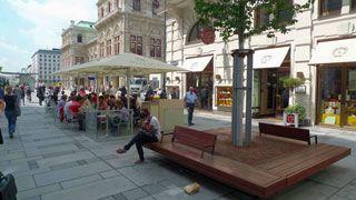 Fußgängerzone, rechts im Vordergrund Sitzbänke um einen Baum angeordnet, dahinter ein Schanigarten mit Sonnenschirmen