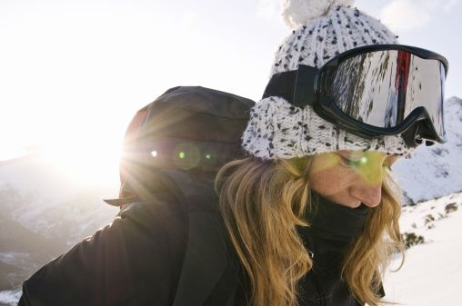 A snowboarder with long blond hair, ski glasses and a glengarry on head, makes a break during the descent of a mountain, Fuente Carrionas massif, Leon, Spain