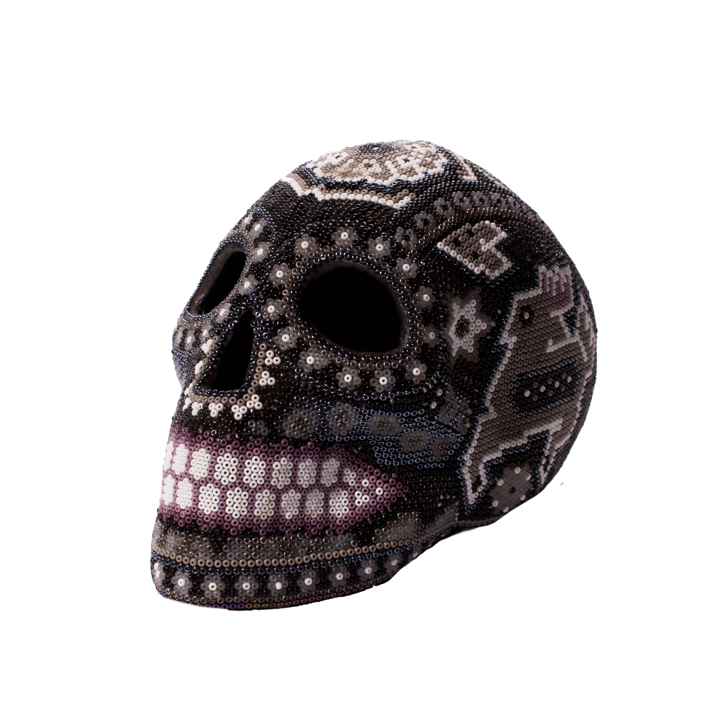 Each bead is hand placed on to this peyote stitch skull from Mexico.  Best kept out of the direct sunlight or extreme heat, as wax is used in the placement of the beads.