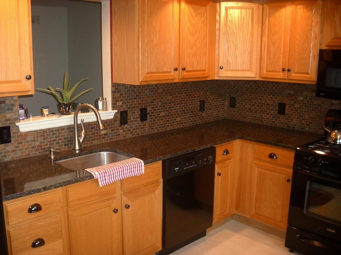 Tile backsplash granite countertop oak colored for Brown kitchen cabinets with black granite