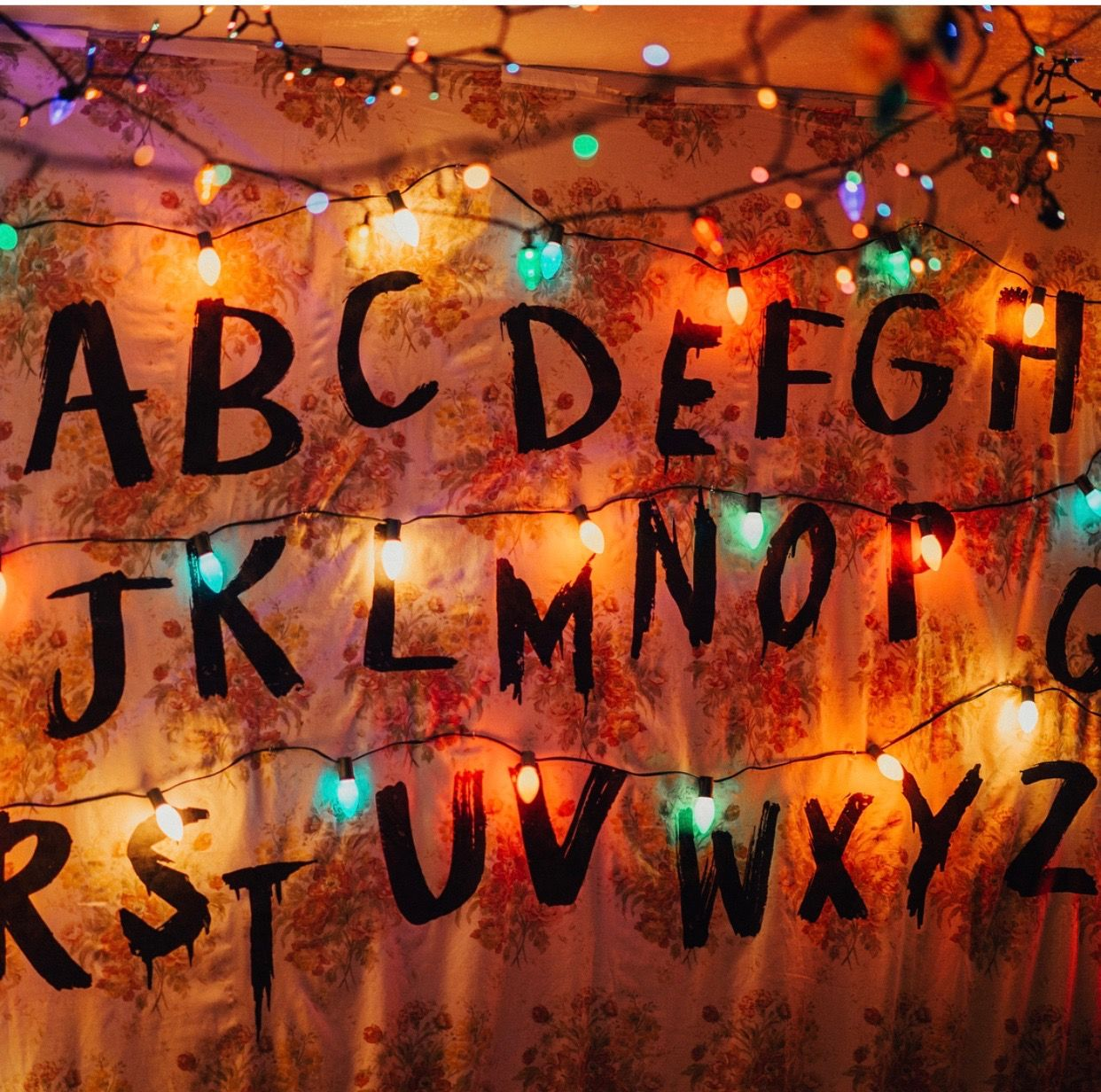 Stranger Things Party Decor Byers Family Room Diy With Floral Sheets Iron On Christmas Lights Wallpaper Stranger Things Christmas Lights Christmas Wallpaper