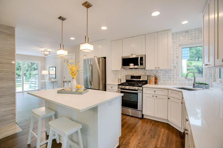 White kitchen heaven! White shaker cabinets, marble backsplash, white quartz countertops, a spacious kitchen island with seating, modern pendant lights, and stainless steel appliances against warm hardwood floors! #pendantlights #kitchenisland #whitecabin #luxurykitchendesigns #whiteshakercabinets