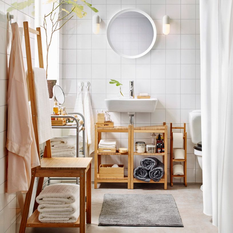 A medium size white bathroom with toilet roll stand, shelves and - decoracion con bambu