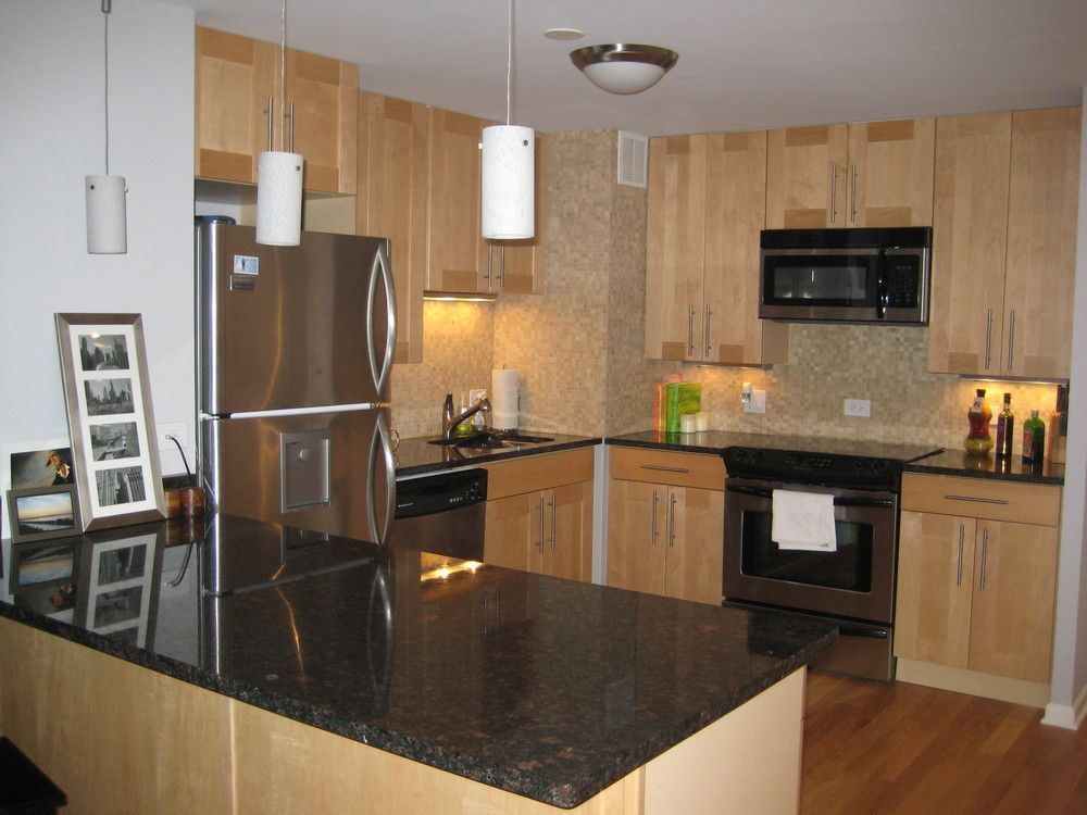 Natural maple cabinets black granite countertop subway for Kitchen cabinets and countertops ideas