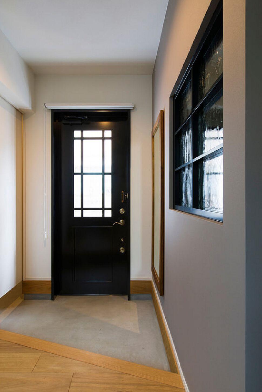 木製の黒い玄関ドアは造作 グレーと白絵お基調とした空間をぐっと
