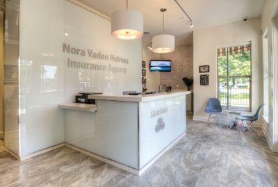 A white, back-painted glass reception area greets visitors at the Nora Vaden Holmes State Farm offices in Metairie.