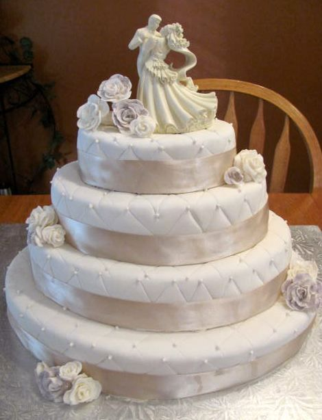 Four Tier White Round Wedding Cake With Flowers And Bride Groom Dancing Topper