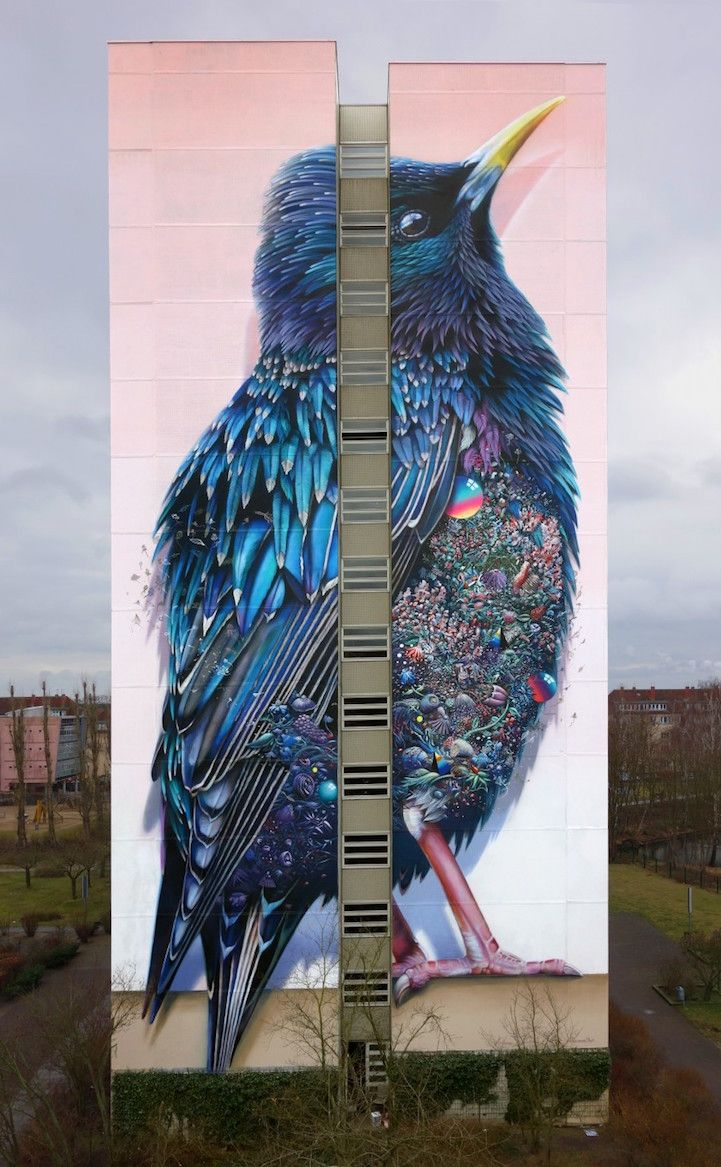 Artists Super A and Collin van der Sluijs collaborated to create a dazzling, 137-foot-tall mural of a bird with iridescent blue feathers and a chest composed of glittering gems and vines.
