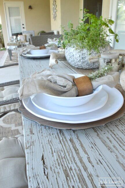Beautiful rustic coastal tablescape! Table & Hearth completely transformed this boring, bare, and beat up patio space into a relaxed, neutral, and weathered coastal-meets-farmhouse space that's perfect for entertianing! Great DIYs and curated decor make it such a beautiful space.