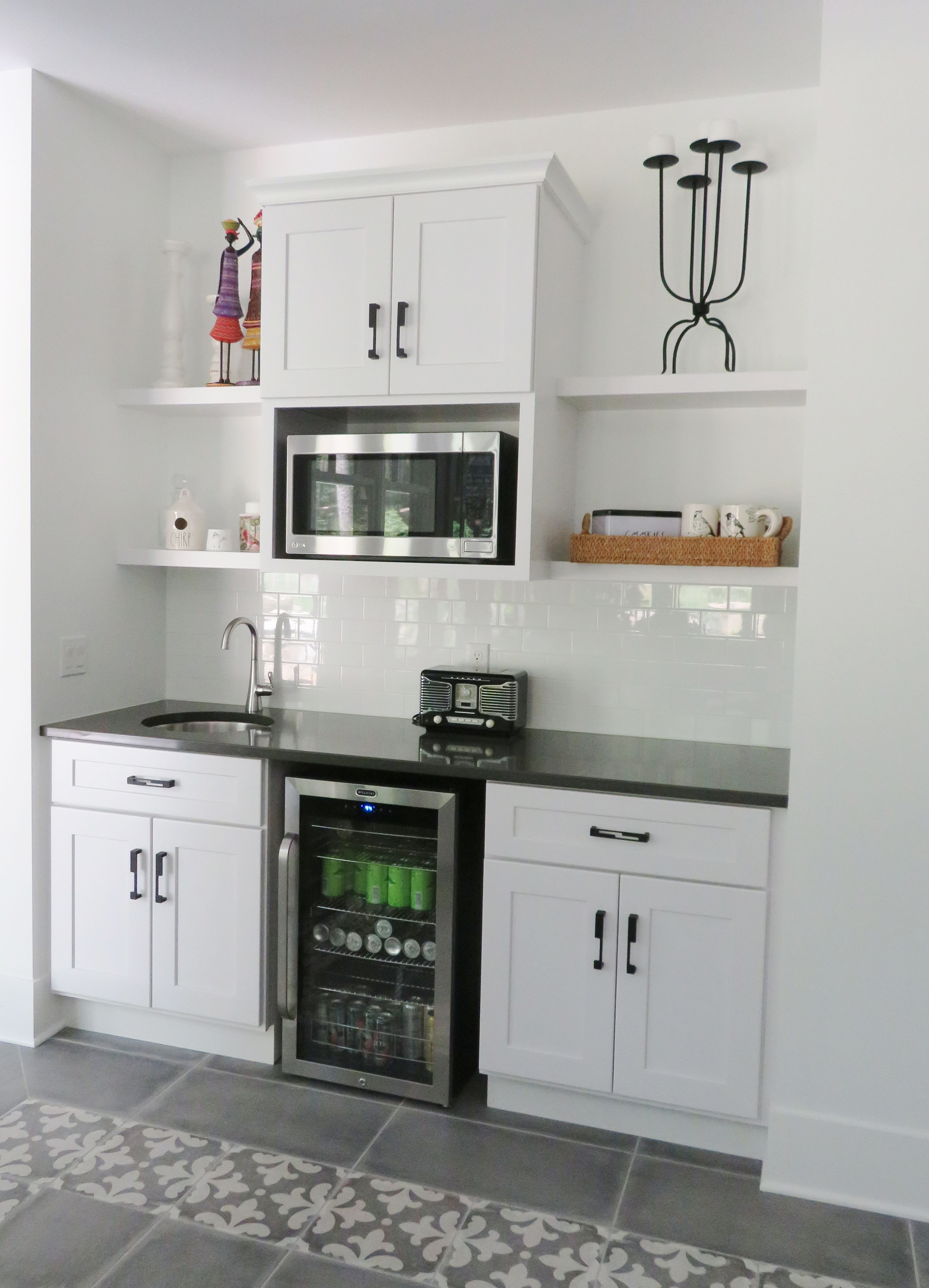 A Basement Wet Bar With Floating Shelves White Cabinetry And Quartz Countertops Small Basement Kitchen Basement Wet Bar Basement Kitchenette