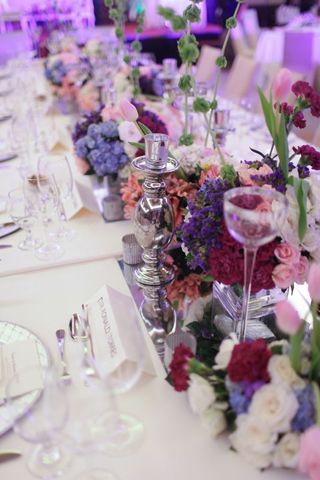 Elegant arrangements of flowers in shades of pink and violet set a romantic atmosphere at this couple's reception. | www.BridalBook.ph #weddings #reception #weddingstyling