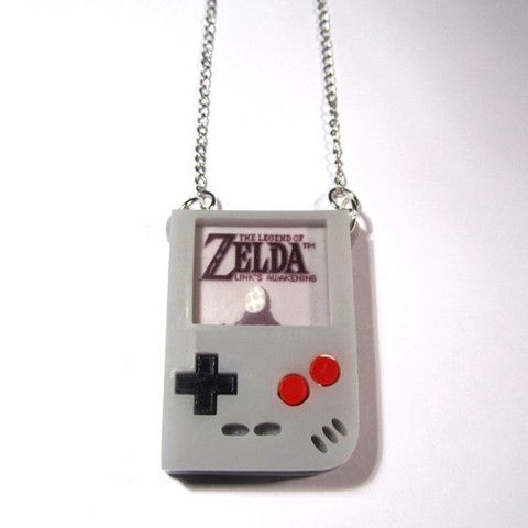 Classic Gameboy Zelda Style Acrylic Necklace. Visit classic gaming roots with this amazing classic Gameboy Zelda style pendant, fashioned from three layers of laser-cut grey acrylic, intricately put together, with a printed game screen and laser-cut game controls. It's a superb piece of 3D jewellery, with extra cool retro pedigree!