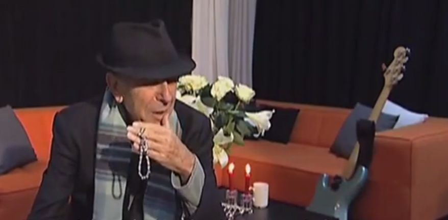 In just over four minutes of this interview shown on Polish TV, some of which is given over to descriptions of him rendered in Polish, Leonard Cohen tells of his 40+ years of association with Poland, his duties at the Mt Baldy Zen Center, his many years of enduring depression, and his dedication to his fans. There are also some interesting shots of Cohen backstage (as in the screenshot atop this post) and during the soundcheck…
