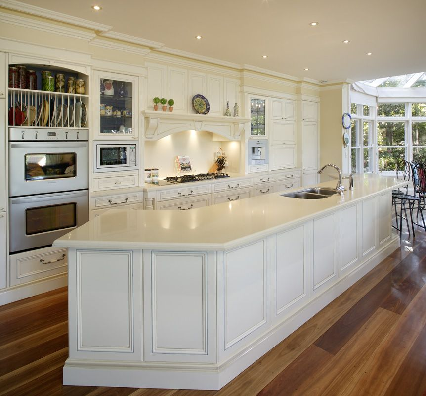 White kitchen with a very large curved benchtop looks for Very large kitchen island