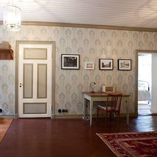 21 - Tässä halli keittiön pariovelta nähtynä. Muistatteko sen kalkkimaalifragmentin? Se on kuvassa näkyvissä ja suojassa valkoisten kehysten sisällä. Kyseessä on siis tavallinen valokuvakehys josta on vain poistettu pohja. Viereiset kuvat seinällä ovat arkistolöytöjä kaupunginmuseon kuva-arkistosta sekä kaupunginarkistosta: Sinikopio rakennuksen pääpiirustuksista vuodelta 1909 ja kaksi arkistovalokuvaa talosta 1920- ja 1930-luvuilta.