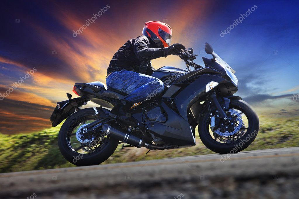 Young Man Riding Motorcycle On Curve Of Asphalt Country Road Aga