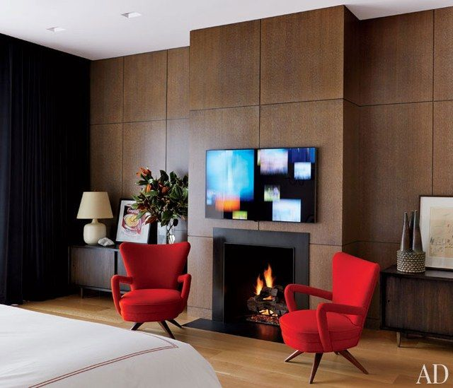 One of the master suite's walls is sheathed with panels of stained oak; the flat-screen television is by Samsung.