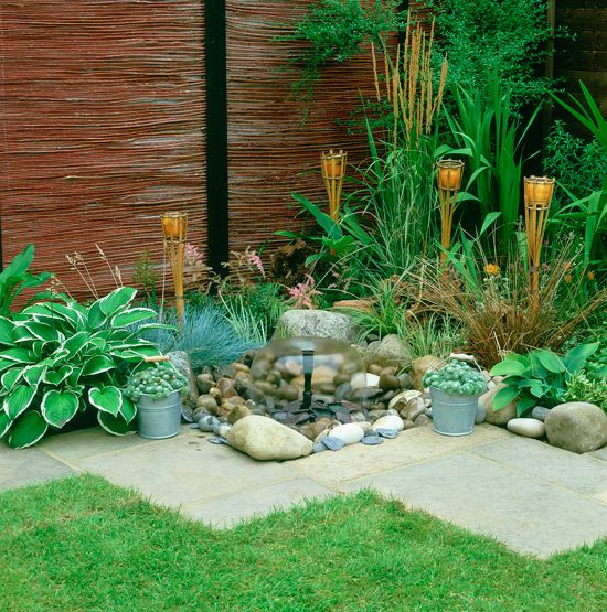 Townhouse garden with flagstone border, bamboo fencing and water feature